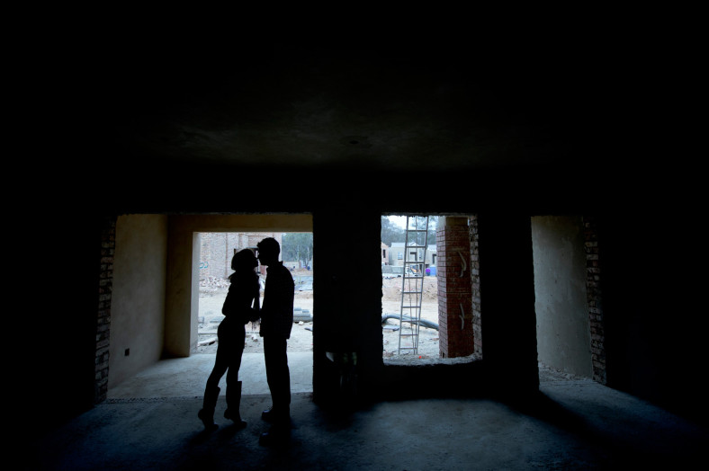 Couple kissing in building site, silhouette