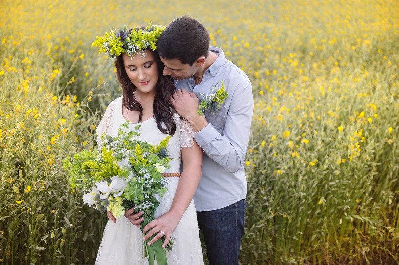 Engagment photo in field of yellow flowers