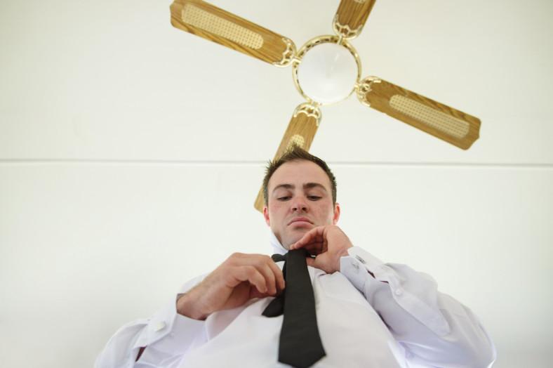 Groom tying tie