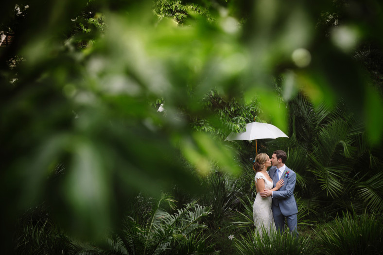 Bride and groom in the tropics with umbrella