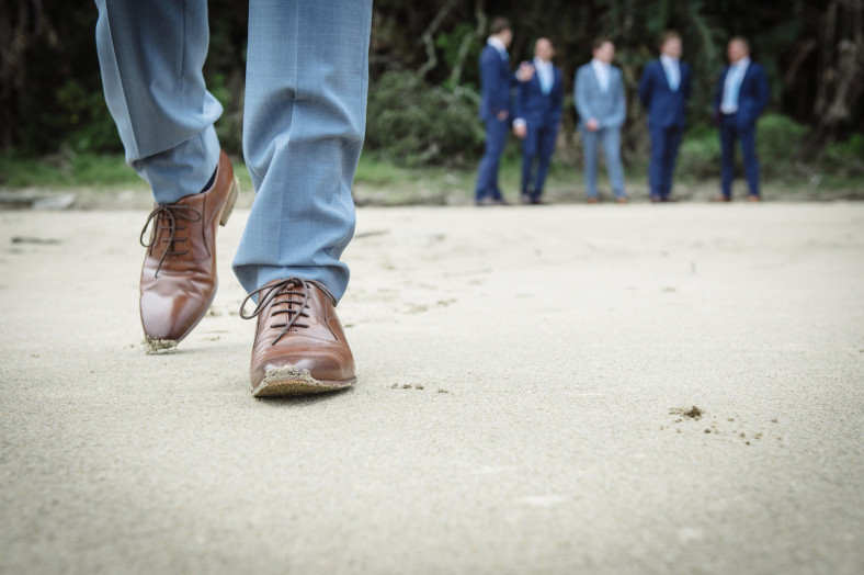 Grooms shoes with groomsmen in the background
