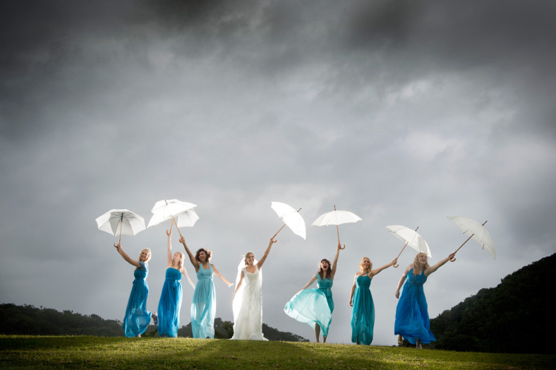 Bridemaids and bride with umbrellas