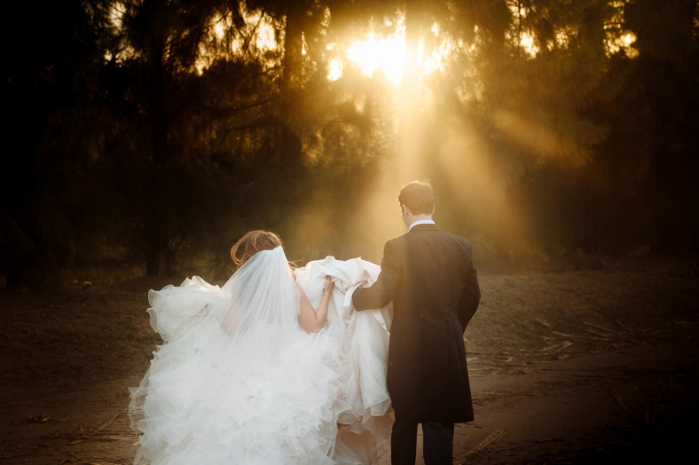 Bride and Groom walking away into light beams