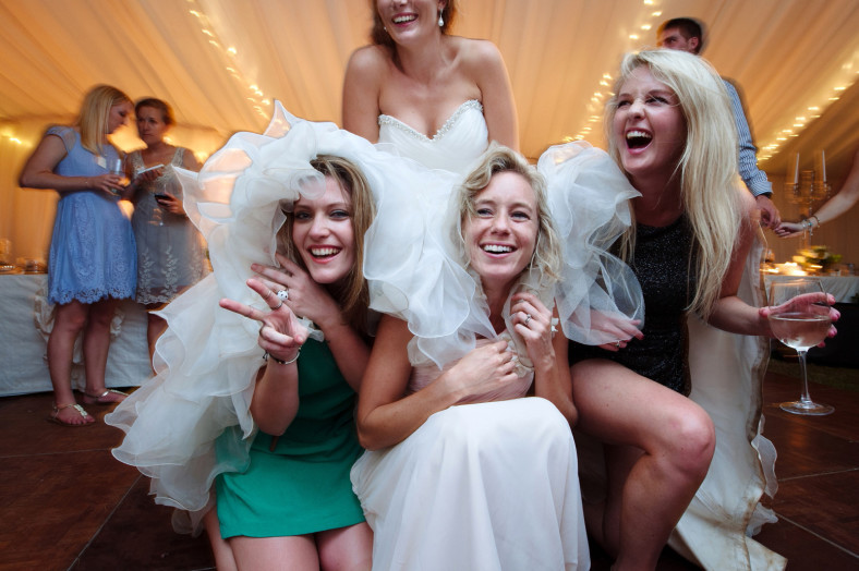 Girls hiding under wedding dress