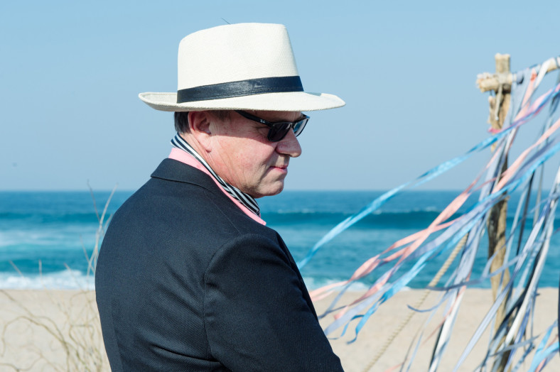 groom with hat at beach wedding