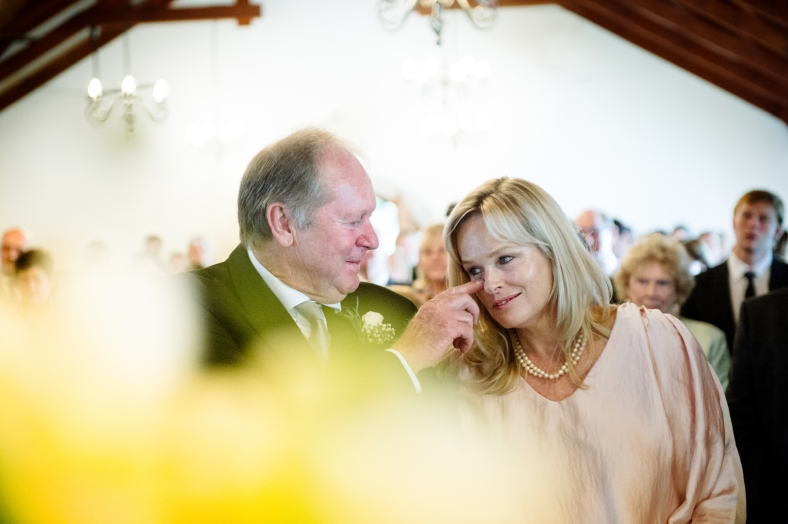 Father of the bride wiping Mother's tear