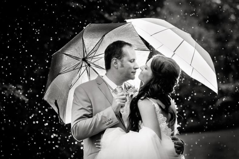 rainy wedding bride and groom with umbrellas