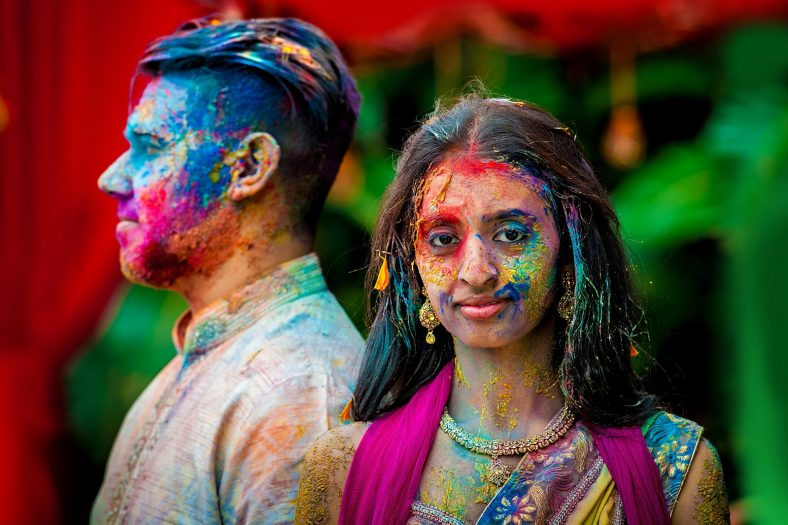Creative Portrait photography of Hindu couple at Wedding Holi Fight.