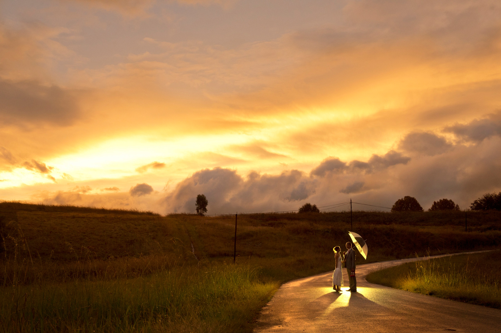 bride and groom on a road at sunset