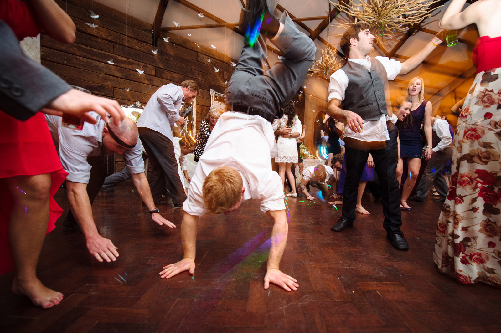 man doing handstand at a wedding