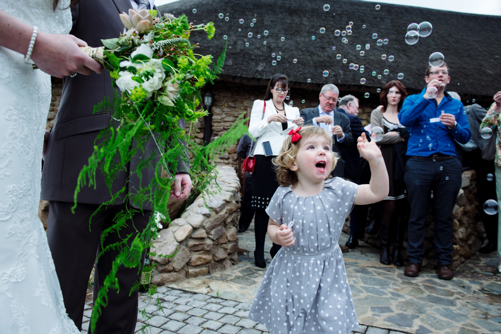 girl blowing bubbles at wedding
