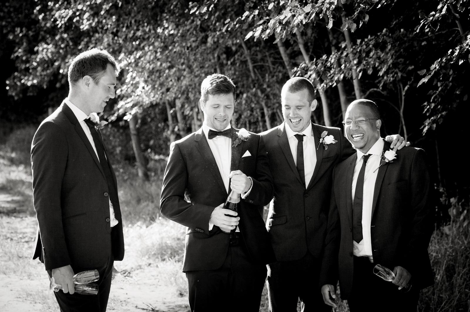 Men popping champagne